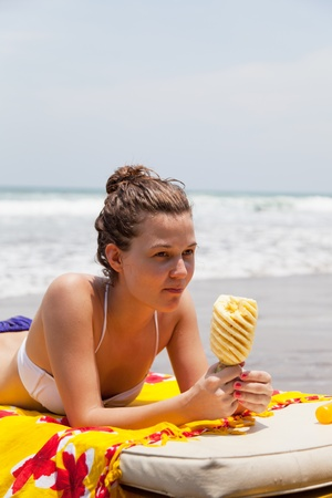 girl lies on a beach plank bed and eats pineapple Stock Photo - 13296464