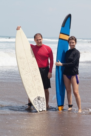Young people with surfboards stand in water photo