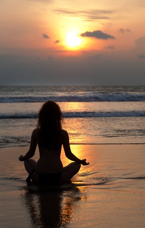 Silhouette d'une femme méditant sur un rocher magnifique de la mer Banque d'images