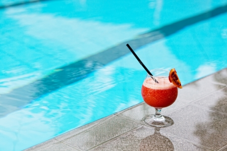 pool side: glass with drink costs on a pool side