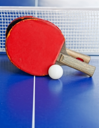 wo table tennis or  rackets and balls on a blue table with net, shallow DOF, focus on rackets  photo