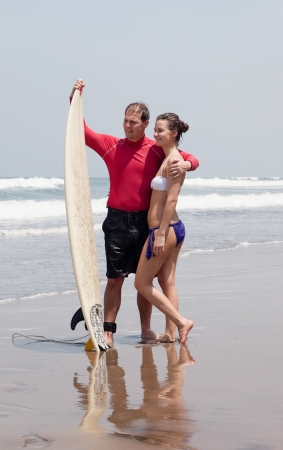 Man embraces the girl and holds surf photo