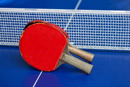 Two table tennis or table tennis rackets and balls on a blue table with net photo