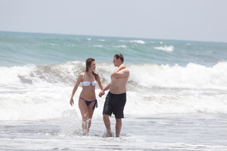 Happy man and the girl go together on an ocean coast photo