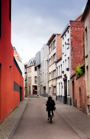 cyclist goes on the ancient narrow street in the Belgian city of Malines (Mechelen) photo