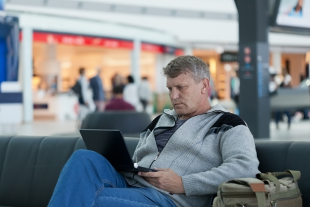 mature man with the laptop in a hall expectation of the international airport photo
