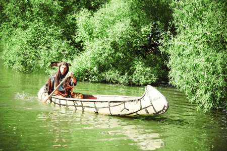North American Indian floats down the river on a canoe