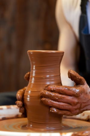 handicrafts: hands of a potter, creating an earthen jar on the circle