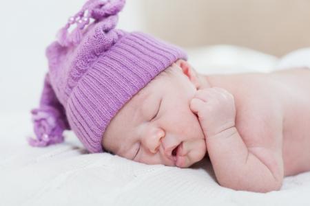 ridicolo: neonato con un cappello viola ridicola posti letto, sdraiata su uno stomaco