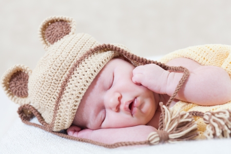 sleeping newborn baby with a ridiculous knitted hat Stock Photo