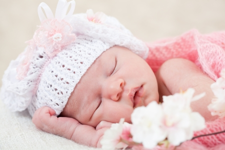 newborn girl sleeps with spring flowers under a knitted pink cape Stock Photo - 14622363