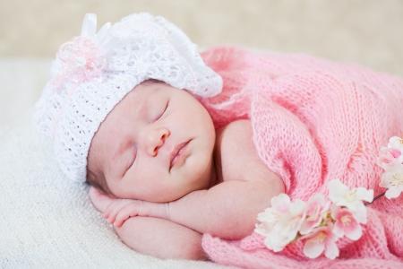 Niña recién nacido duerme con flores de primavera bajo una capa de punto rosa Foto de archivo - 14622349