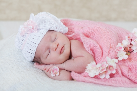 newborn girl sleeps with spring flowers under a knitted pink cape photo
