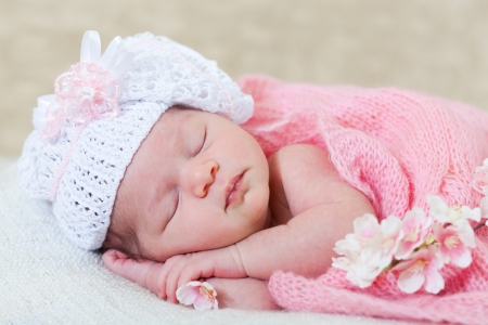 newborn girl sleeps with spring flowers under a knitted pink cape Stock Photo