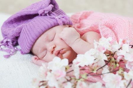 baby nursery:  newborn girl in a violet hat sleeps under a pink cape Stock Photo