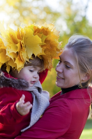 Happy mother with the daughter walk in autumn park photo