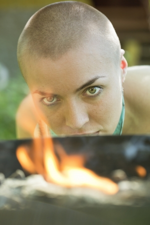 bald girl: bald girl looks at fire