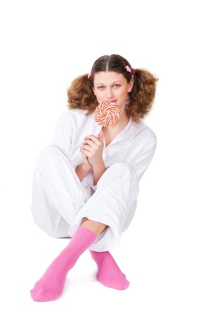 girl in a light pajamas sits with sugar candy, is isolated, a white background photo