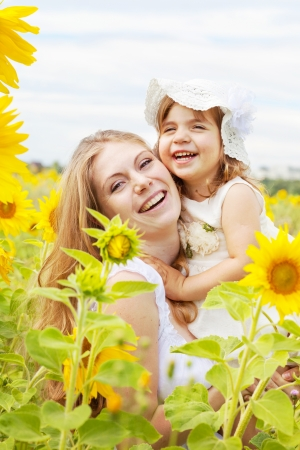 Happy mother with the daughter in the field with sunflowers photo