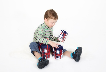 boy sits and plays with gift boxes photo