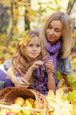 Happy mum et le parc automne fille jeu sur le feuillage tombé