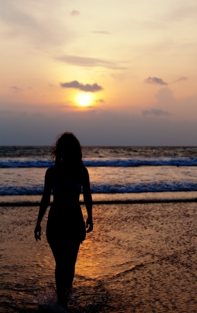 Silhouette of the girl with a flying hair, running across the ocean at sunset  photo