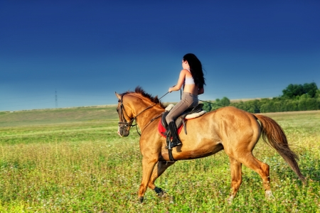 Beautiful girl riding a horse in countryside Stock Photo