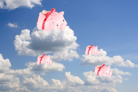 Pigs-coin boxes sit on white clouds in the blue sky photo