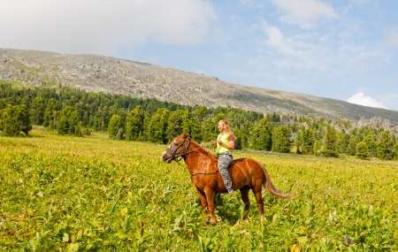 Happy girl riding a horse bareback at mountains  Stock Photo