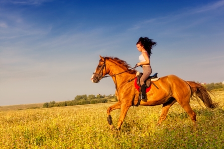 riding horse: Beautiful girl riding a horse in countryside Stock Photo