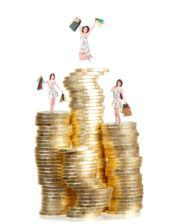 a lot of money:  happy girl with purchases on columns of gold coins Stock Photo