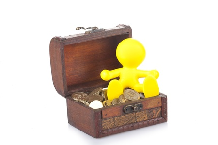 toy yellow little man sits on a chest with money Stock Photo - 15507290