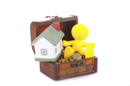 toy yellow little man sits on a chest with money and the house Stock Photo - 15507291