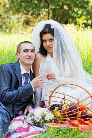 marriageable: groom with  bride sit on a grass and eat a juicy water-melon Stock Photo