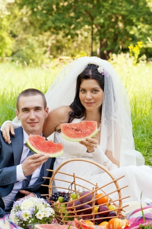 groom with  bride sit on a grass and eat a juicy water-melon Banque d'images