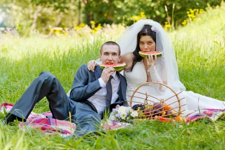 groom with  bride sit on a grass and eat a juicy water-melon photo