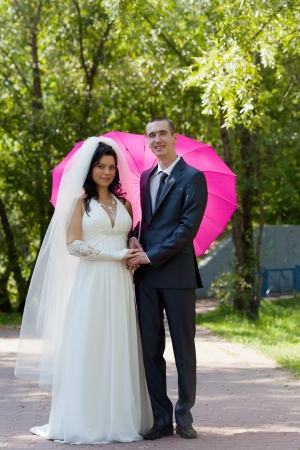 Newly-married couple in a summer garden under a pink umbrella in the form of heart photo