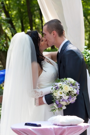 Newly-married couple kiss after ceremony of wedding