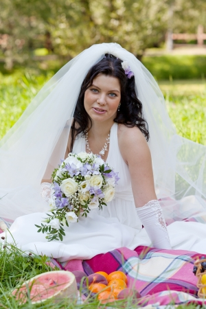 marriageable: beautiful bride sits on a grass with a big basket with fruit