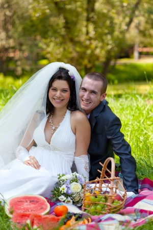groom and the bride sit on a grass with a big basket with fruit photo