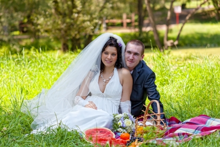 marriageable: groom and the bride sit on a grass with a big basket with fruit