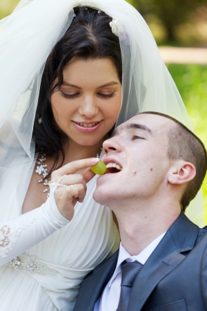 marriageable: happy bride treats the groom with grapes