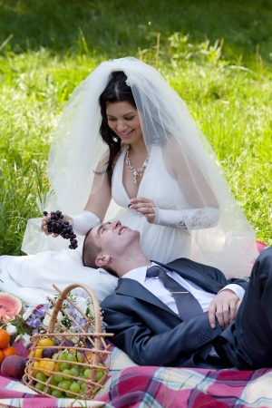 happy bride treats the groom with grapes photo