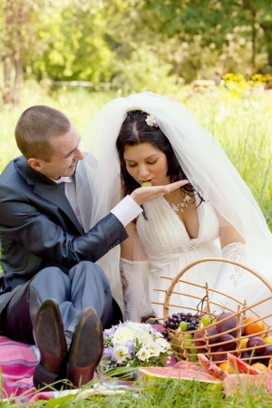 happy groom treats the bride with ripe grapes photo