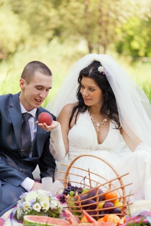 bride treats the groom with a ripe peach photo
