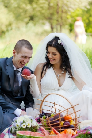 bride treats the groom with a ripe peach