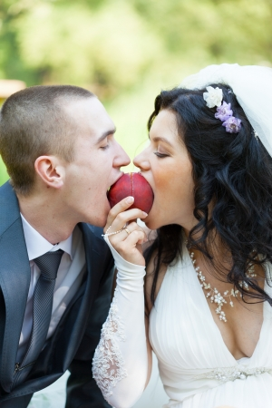 groom and the bride together eat a ripe peach photo