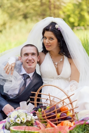 groom and the bride together sit on a grass with a big basket of fruit