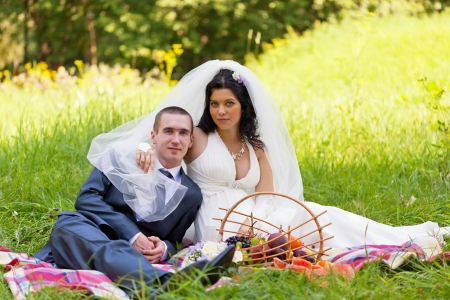 groom and the bride sit on a grass with a big basket with fruit