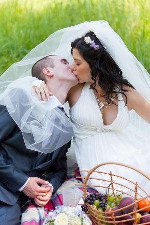 groom and the bride together sit on a grass with a big basket of fruit and kiss photo